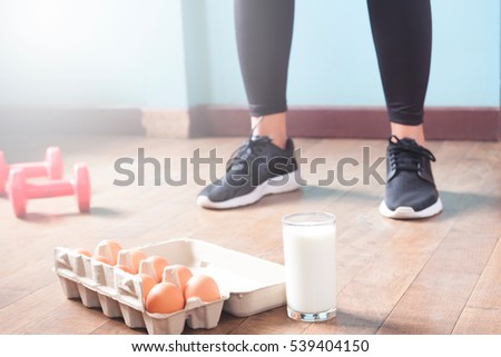 Fitness female in black pants standing on wood floor with dumbbells and dairy product for workout with copy space
