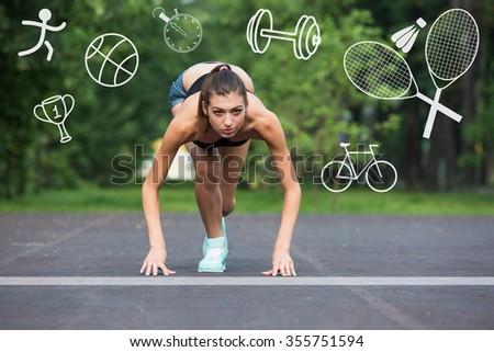 Fitness female runner in ready start line pose outdoors in summer sprint challenge. - stock photo
