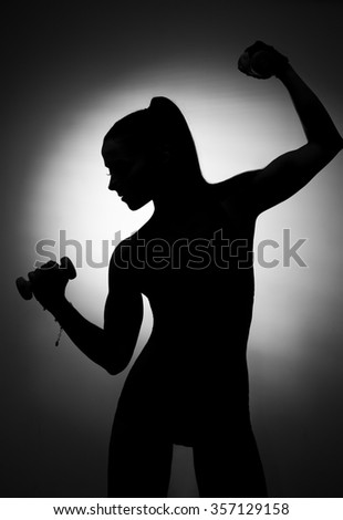 Fitness female with muscular body doing workout with dumbbells, black background. Trained female body, black and white. Woman with beautiful athletic body doing exercises with dumbbells,bodybuilding - stock photo