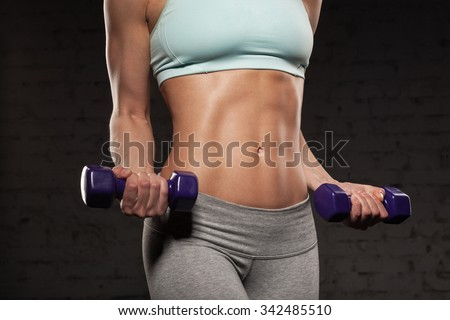 Fitness female woman with muscular body, do her workout with dumbbells, abs, abdominals - stock photo