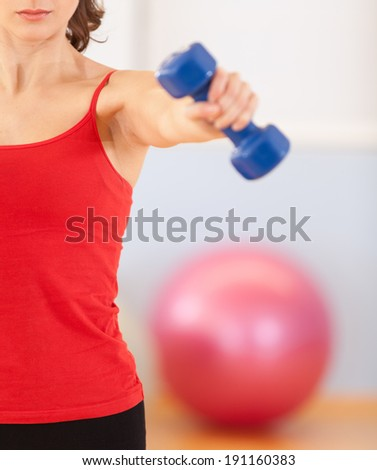 Fitness. Fitness instructor in the gym. Holding dumbbells.