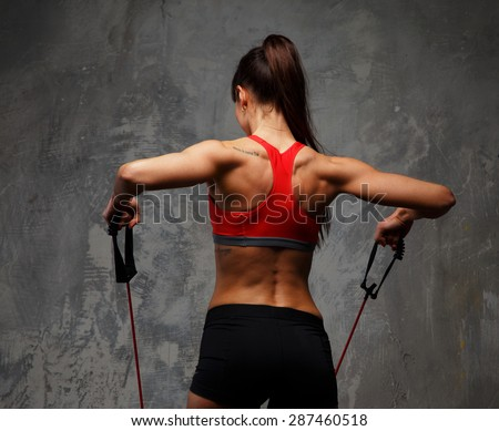 Fitness foman from back doing exercises with expander. - stock photo