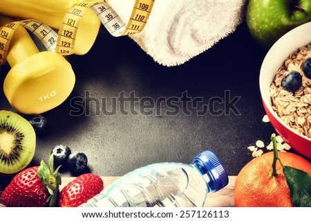 Fitness frame with dumbbells, water bottle and fresh fruits. Healthy lifestyle concept with copy space