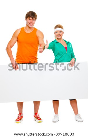 Fitness girl and male athlete with blank billboard and showing thumbs up