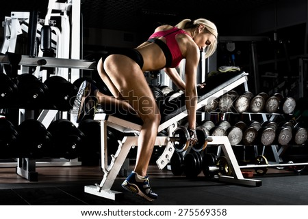 fitness girl  execute exercise with  dumbbells, on broadest muscle of back - stock photo