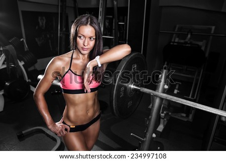 fitness girl exercising with barbell in gym - stock photo
