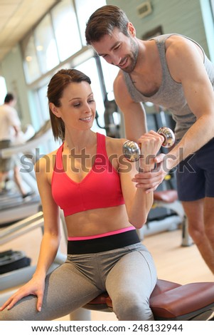 Fitness girl exercising with coach - stock photo