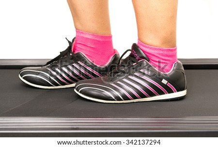 Fitness girl fast running on treadmill. Woman with muscular legs on white background - stock photo