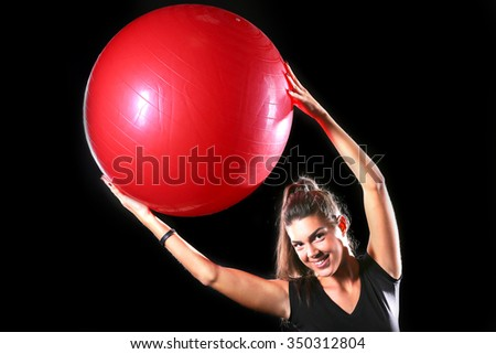 fitness girl lifting red fitness ball isolated on black background - stock photo
