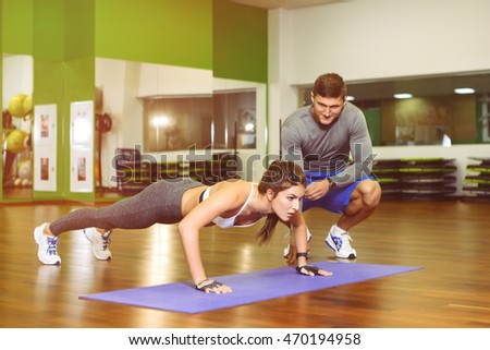 fitness, girl pushed in the gym under the supervision of a trainer. The concept of Health, sports