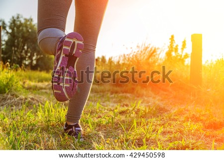 Fitness Girl running at sunset in a path surrounded by fields with colorful outfit