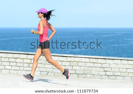 Fitness girl running fast on summer day with sea on background. Beautiful female athlete exercising. - stock photo