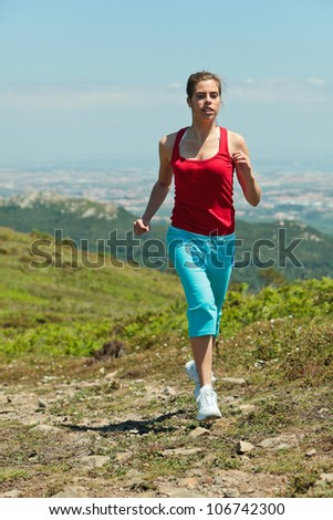 Fitness girl running on path in mountains