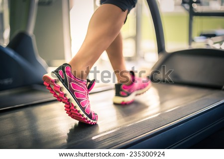 Fitness girl running on treadmill. Woman with muscular legs in gym - stock photo