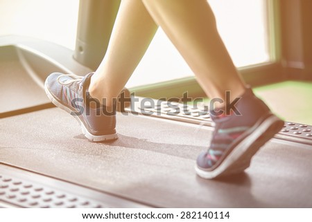 Fitness girl running on treadmill. Woman with muscular legs in modern gym