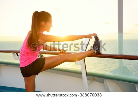 Fitness girl stretching leg on cruise vacation. Young woman adult doing stretches after running workout at sunset on balcony of a cruise ship during summer holidays. Active lifestyle. - stock photo