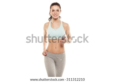 fitness girl with a smartphone on a white background, enjoys sports training, gym workout - stock photo
