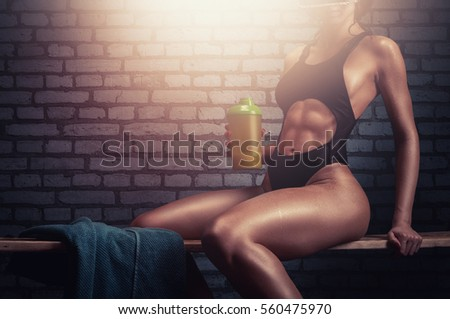 Fitness girl with athletic body taking a break after core strenght training in the gym.