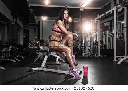 fitness girl with shaker posing on bench in the gym - stock photo