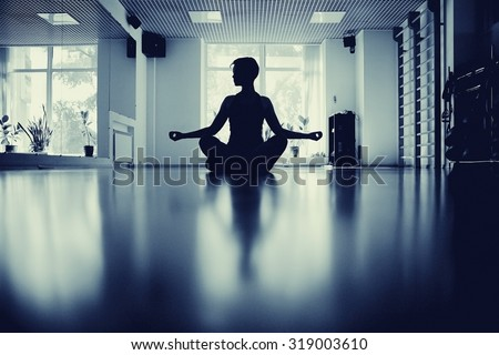 fitness girl yoga silhouette in the room - stock photo