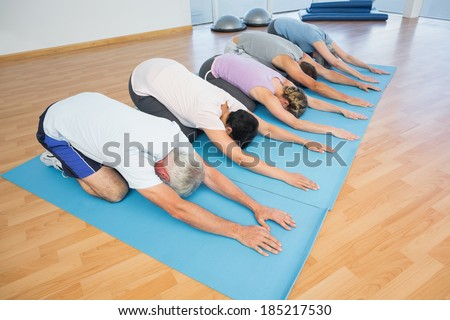Fitness group bowing in row at the yoga class - stock photo