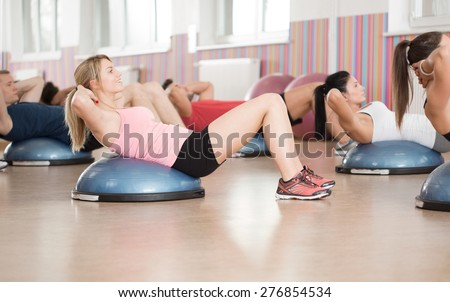 Fitness group doing abs exercise on bosu ball - stock photo
