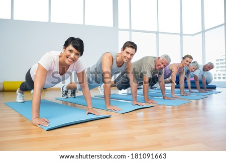 Fitness group doing push ups in row at the yoga class