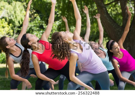 Fitness group doing yoga in park on a sunny day - stock photo