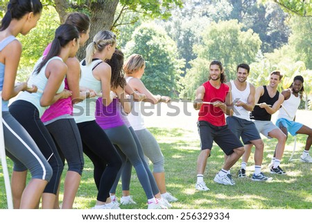 Fitness group playing tug of war on a sunny day - stock photo