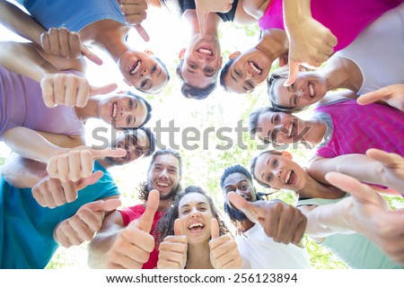 Fitness group smiling at camera in park on a sunny day - stock photo