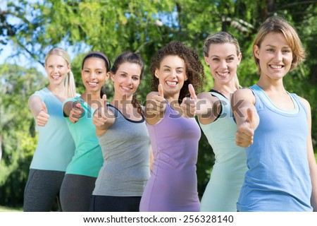 Fitness group smiling at camera on a sunny day - stock photo