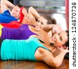 Fitness group with instructor in gym doing stomach crunches for sport - stock photo