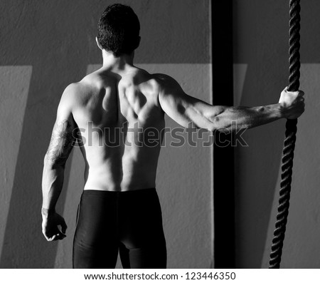 Fitness gym man holding hand a climbing rope rear view - stock photo
