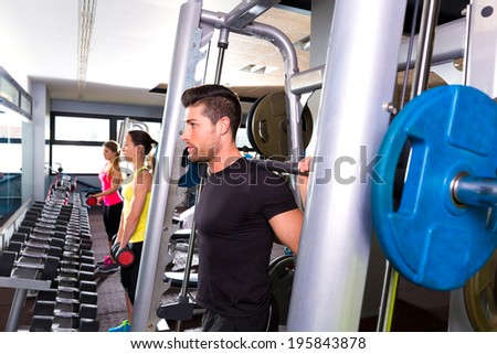 Fitness gym man multipower system weightlifting barbell and dumbbell women - stock photo