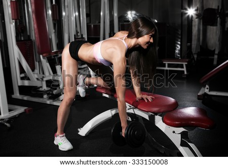 Fitness gym woman strength training lifting dumbbell weights in Bent-over One-Arm Dumbbell Row. Female fitness girl exercising indoor in fitness center. Beautiful fit mixed race Asian Caucasian model. - stock photo