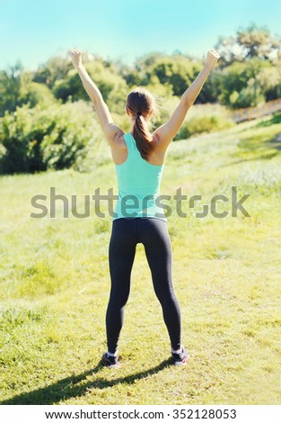 Fitness happy runner woman enjoying after training in park, runner winner, raises hands up, sport and healthy lifestyle, view back