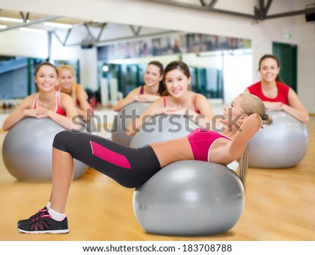 fitness, healcare and dieting concept - young woman doing exercise on fitness ball - stock photo