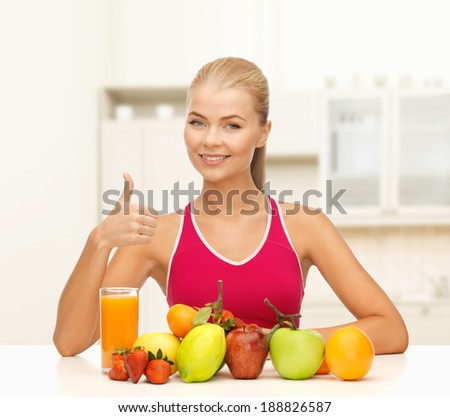 fitness, healthcare and diet concept - smiling young woman with organic food or fruits on table shwoing thumbs up