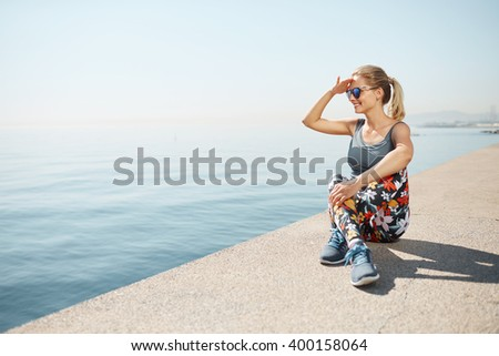 Fitness healthy blonde woman runner relaxing after city running and workout outdoors. Young Caucasian fit girl looking and enjoying view of deep sea. - stock photo