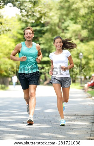 Fitness healthy lifestyle young couple training for marathon outside in Central Park, Manhattan, New York. Asian female model and Caucasian handsome sport fitness male. Happily enjoying jogging. - stock photo