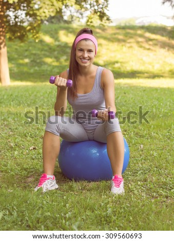 Fitness Healthy Smiling Young Woman doing exercise on pilates ball with dumbbells at beautiful summer day in the park. Outdoor activity sporty lifestyle.