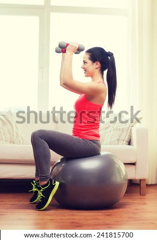 fitness, home and diet concept - smiling girl exercising with fitness ball and dumbbells at home - stock photo
