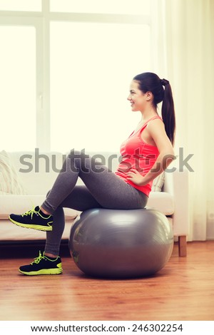 fitness, home and diet concept - smiling girl exercising with fitness ball at home - stock photo