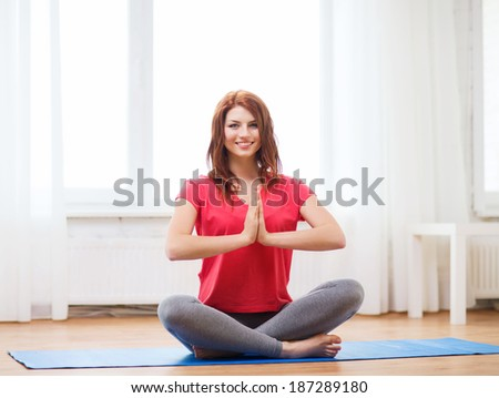 fitness, home and diet concept - smiling redhead teenager meditating at home - stock photo