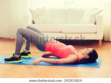 fitness, home and diet concept - smiling teenage girl doing exercise for legs and buttocks on floor at home - stock photo