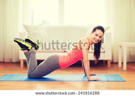 fitness, home and diet concept - smiling teenage girl doing push-ups at home - stock photo