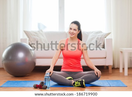 fitness, home and diet concept - smiling teenage girl sitting on mat with sports equipment at home - stock photo