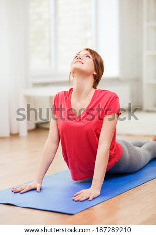 fitness, home and diet concept - smiling teenage girl streching at home - stock photo