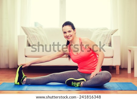 fitness, home and diet concept - smiling teenage girl streching on floor at home - stock photo