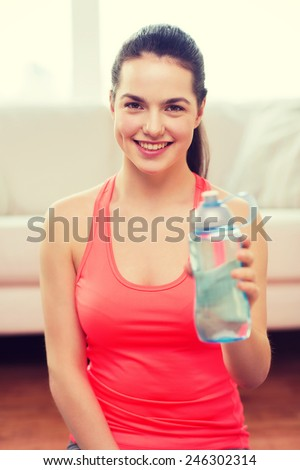 fitness, home and diet concept - smiling teenage girl with bottle of water after exercising at home - stock photo